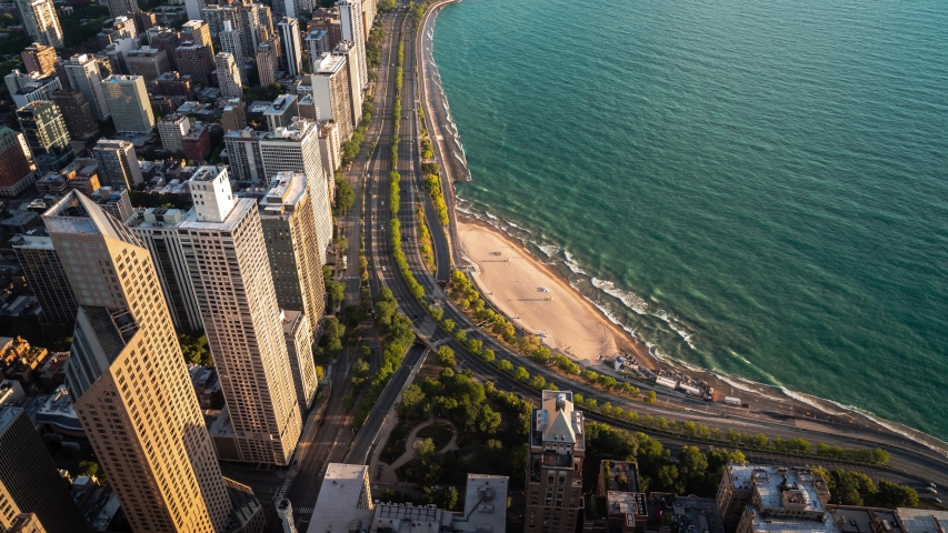 Panning up aerial time lapse looking down on building rooftops and the Oak Street curve on Lake Shore Drive and the warm sandy beach in Chicago early on a summer morning as waves roll into the shore.