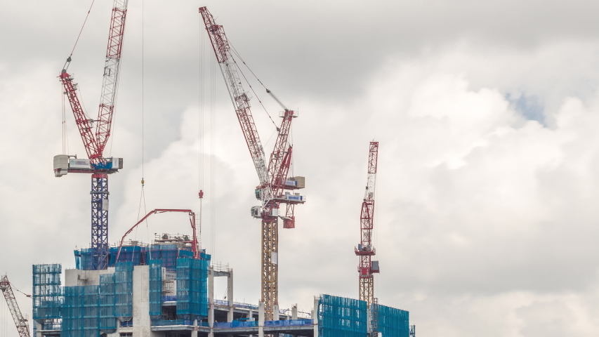 Working cranes on a modern office building under construction against cloudy sky in Singapore timelapse. Asian urban development and construction concept. Industrial background. Royalty-Free Stock Footage #1058319268