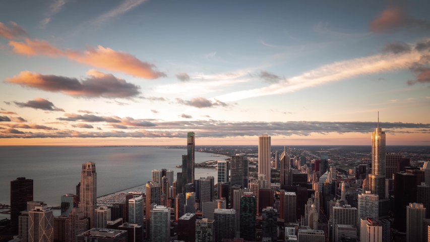Beautiful panning down sunrise aerial time lapse of Chicago skyline with pink and orange clouds moving over the water of Lake Michigan and high rise buildings downtown early on a summer morning.