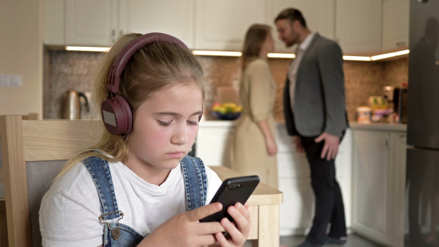 Family scandal. Parents quarrel. The child try to be distracted and not hear. | Shutterstock HD Video #1058324353
