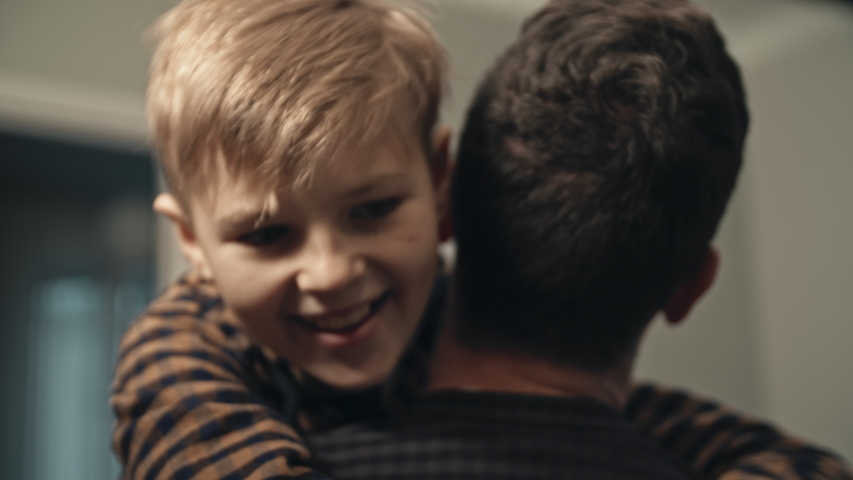 Smiling son meeting his dad at the door in the evening. Concept of joy. Close-up of happy teenage son in casual clothes runnig to his father and hugging him. Young dad finally coming home from work. Royalty-Free Stock Footage #1058324653