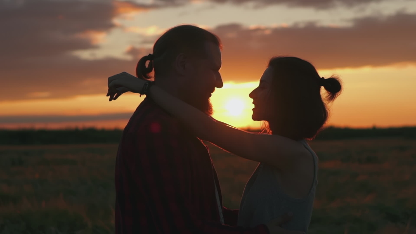 Silhouette of kissing couple in golden sun and beautiful sunset. Young and romantic family enjoying. Man and woman in love on holidays on summer evening. People talking and hugging by heart.