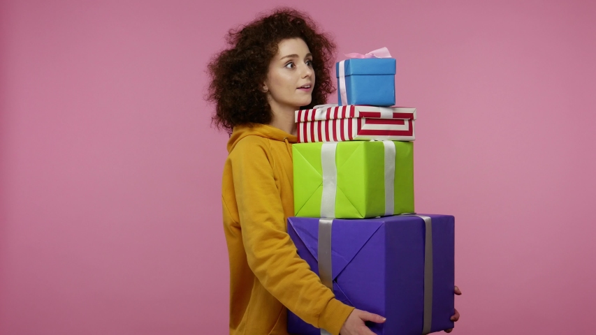 Amazed astonished young woman afro hairstyle in hoodie looking surprised at mount of boxes in her hands, shocked by unbelievable birthday gifts, lot of presents. studio   isolated on pink background | Shutterstock HD Video #1058324953