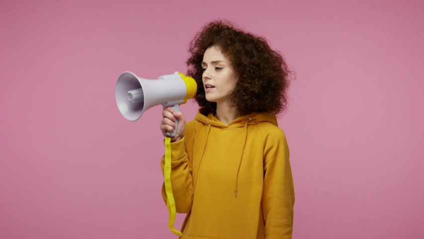 Funny young woman afro hairstyle in hoodie talking with megaphone, proclaiming news, loudly announcing advertisement, warning using loudspeaker to shout speech. studio shot isolated on pink background Royalty-Free Stock Footage #1058324956