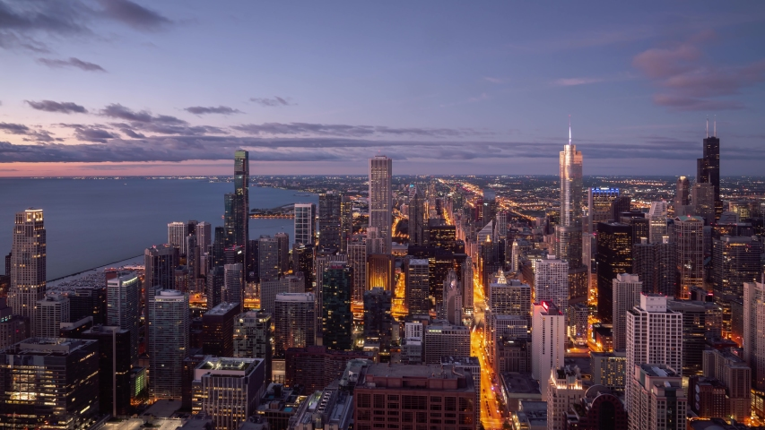 Panning up night time aerial timelapse of Chicago skyline with pink and blue clouds in the sky floating over the water of Lake Michigan and the high rise skyscrapers in downtown along Michigan Avenue.