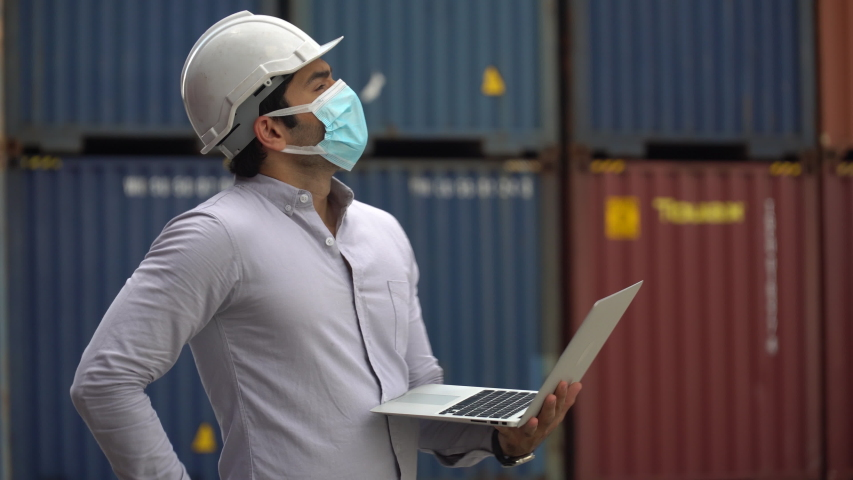 Foreman wareing face mask holding laptop computer talking on the walkie-talkie control loading Containers box at warehouse logistic in Cargo . during coronavirus pandemic or covid 19 outbreak  | Shutterstock HD Video #1058325859