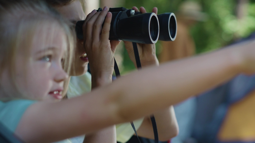 Two curious brother and sister using binoculars watching animals in the woods. Little explorers. Adventure. Camping in forest. Childhood concept.