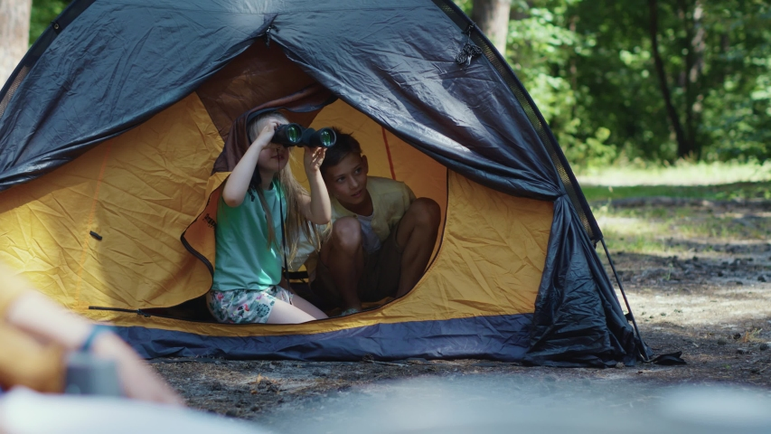 Young active adorable two kids brother and sister sitting and hiding inside camp playing explorers watching wild animals in binoculars. Children. Adventures. Camping.