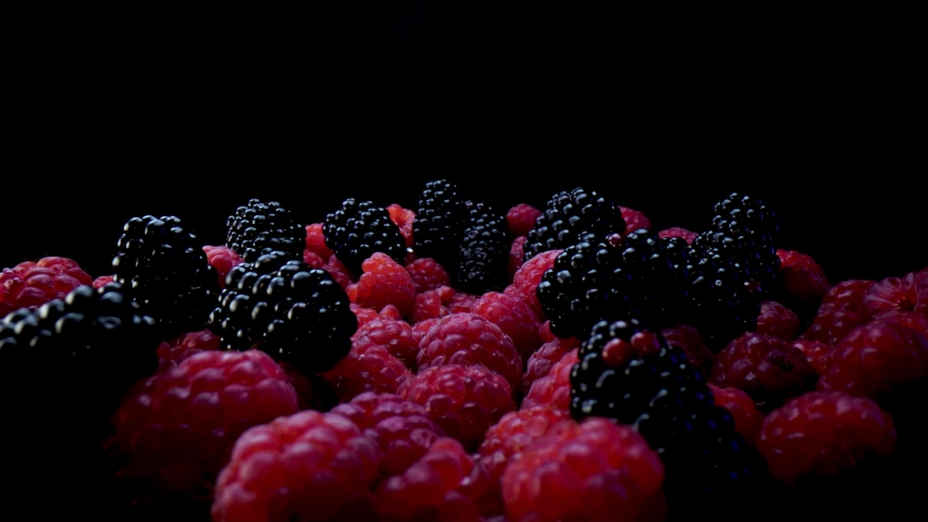 Blackberries and raspberries on a black background. Composition of a raw and fresh forest fruits close up in 4K. | Shutterstock HD Video #1058326873