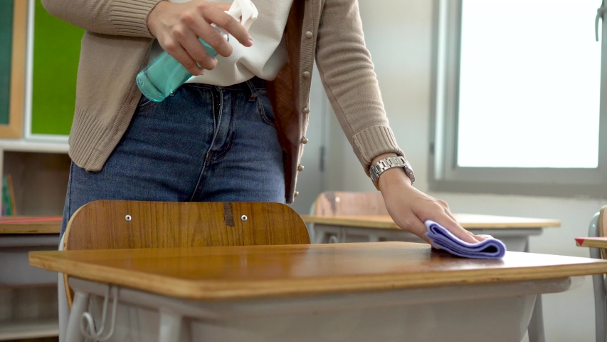 Young female teacher using an alcohol spray to disinfect student desks in classroom. Woman in face mask cleaning the tables with antiseptic sanitizer. School reopen after quarantine and lockdown. Royalty-Free Stock Footage #1058326948