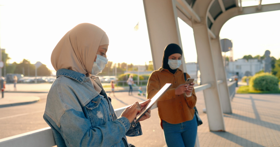Muslims young pretty women in traditional headscarves standing outdoors and using gadgets. Arabic females in medical masks tapping and scrolling on mobile phone and tablet device. Arabs girls in city.