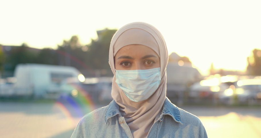 Portrait shot of young Muslim beautiful woman in traditional headscarf and medical mask looking at camera. Close up of Arabian female in hijab at street in sunlight. Arab girl. Royalty-Free Stock Footage #1058327770