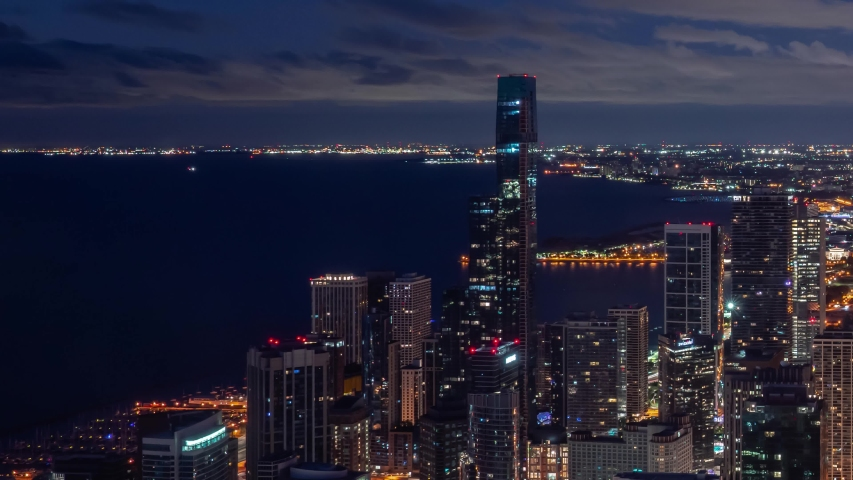 Zoom out night time aerial timelapse of Chicago skyline with pink and blue clouds in the sky floating over the water of Lake Michigan and the high rise skyscrapers in downtown along Michigan Avenue.