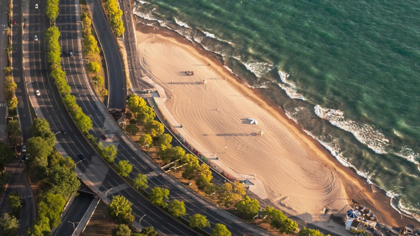 Zoom out aerial time lapse looking down on building rooftops and the Oak Street curve on Lake Shore Drive and the warm sandy beach in Chicago early on a summer morning as waves roll into the shore.