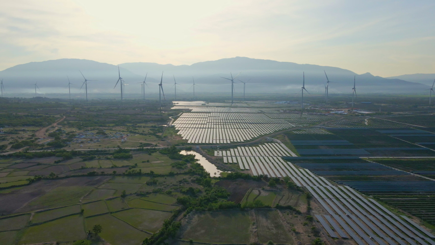 Aerial shot of a huge solar power plant mixed with wind turbines in a big field. Electricity generation from solar energy and wind. Green energy and zero emissions concept Royalty-Free Stock Footage #1058331841