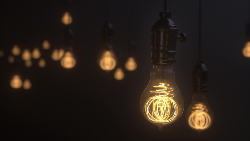 Edison lamps. Vintage light bulb pulsing light in the darkness. Burning retro light bulbs on black background. Depth of field. Concept of new idea, realization or discovery. 3d animation