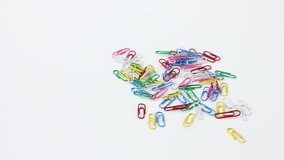 Different office supplies paper clips on white rolling table background.