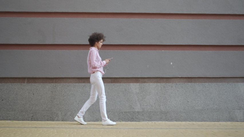 Smiling young european woman walking on urban city street against grey wall holding smart phone. Happy millennial curly lady wearing earphones using mobile apps listening music on cellphone outdoor. | Shutterstock HD Video #1058340631