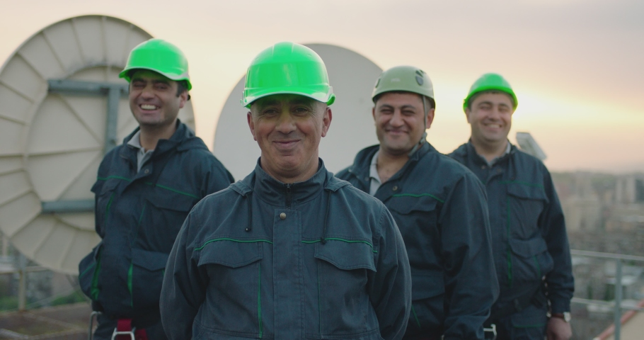 Portrait of group of professional telecommunication industry engineers smiles and looks at the camera . Workers wearing safety uniform and hard hat on unfocused background with sky and antennas . Royalty-Free Stock Footage #1058342944