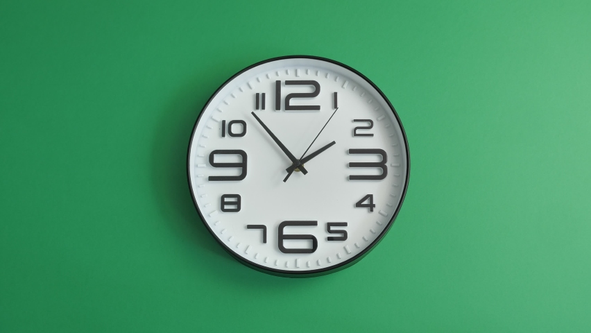 Single white office clock hanging on green background