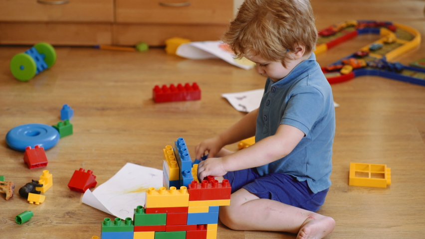 Funny curly baby boy with educational toy blocks. Children play at day care or preschool. Mess in kids room. Toddlers build a tower in kindergarten. Child playing with colorful toys. | Shutterstock HD Video #1058356429