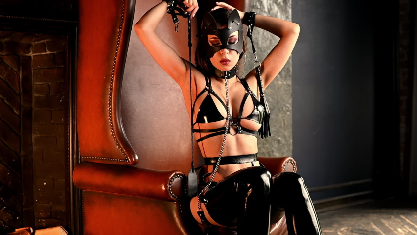 young woman wears sexy leather costume and mask sitting on a chair in the room. Panning camera movement. Strokes her body with a whip. Bdsm concept. No nude.