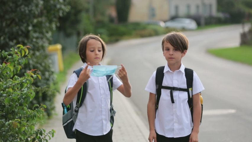 School children, boys, going back to school after the summer vacation, kids going to school wearing medical mask due to coronavirus COVID 19 Royalty-Free Stock Footage #1058360704