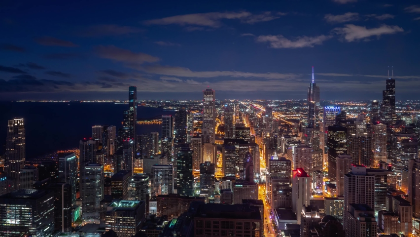 Beautiful night time aerial timelapse of Chicago skyline with pink and blue clouds in the sky floating over the water of Lake Michigan and the high rise skyscrapers in downtown along Michigan Avenue.