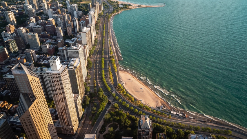 Beautiful aerial time lapse looking down on building rooftops and the Oak Street curve on Lake Shore Drive and the warm sandy beach in Chicago early on a summer morning as waves roll into the shore.