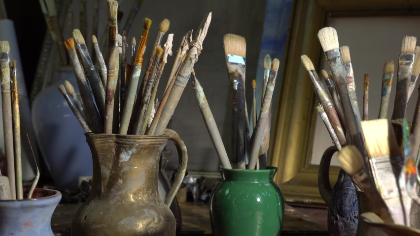 Artist's art tools in the Studio. Oil paintings in creative workroom. Brushes, paints, palette, canvas, easel