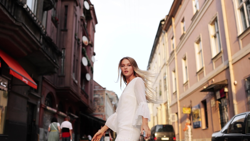 Attractive young lady walking on city street, she turns to camera and smiles. Outdoor portrait happy female tourist having good time wandering around town in summer Royalty-Free Stock Footage #1058366317