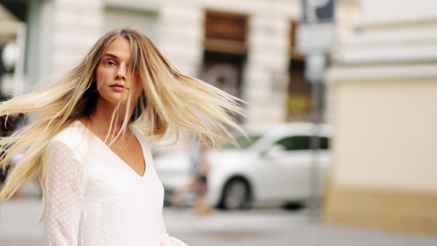 Young beautiful blonde woman in a white dress spinning in the center of a city. Attractive fashion model with flying hair. Beautiful girl woman shakes hair. Slow motion | Shutterstock HD Video #1058366341