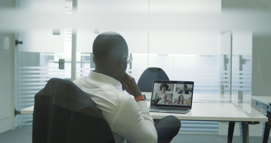 Businessman in empty meeting room using Video Conferencing technology on laptop talking to colleagues working from home Royalty-Free Stock Footage #1058373571