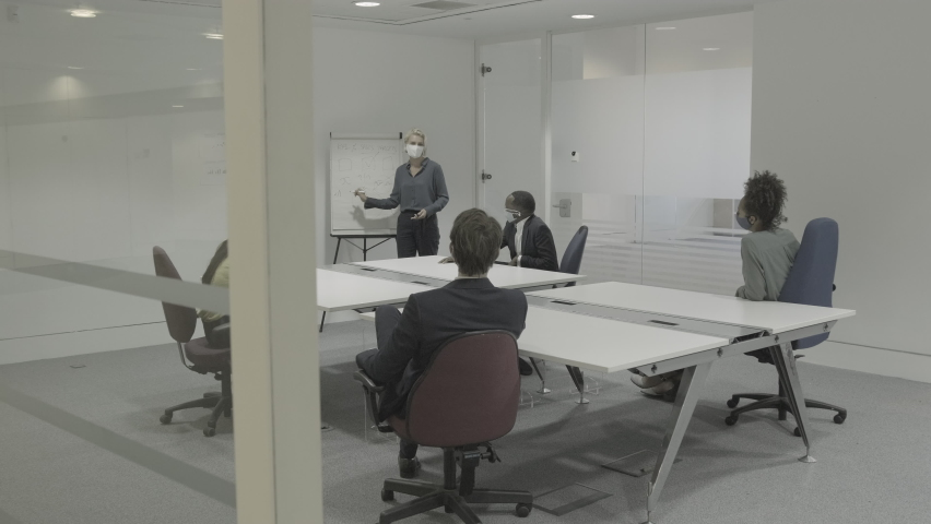 Business people meeting in boardroom wearing protective face mask for presentation Royalty-Free Stock Footage #1058373613