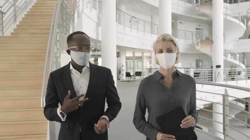 Business people wearing face mask meeting in modern corporate office lobby and walking Royalty-Free Stock Footage #1058373661