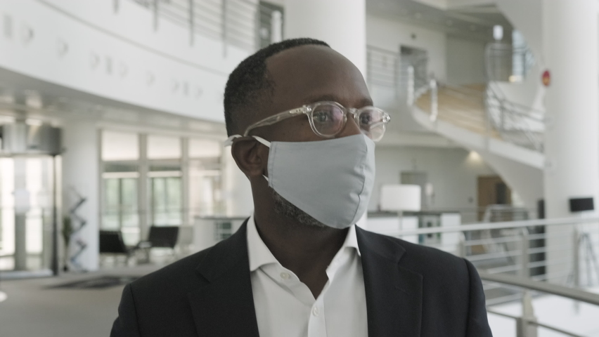 Businessman wearing face mask and walking in office lobby on way to meeting   Shutterstock HD Video #1058373676