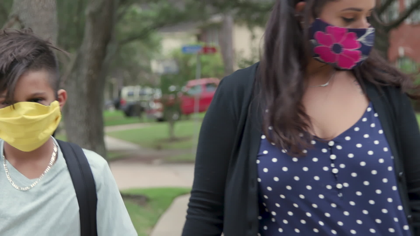 Prerequisite for in classroom instruction and the new normal during COVID19 pandemic is mask wearing as demonstrated by this mother and her children as she walks them to the school bus stop. Royalty-Free Stock Footage #1058373982