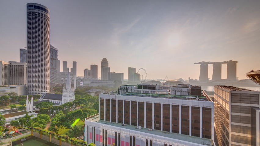Sunrise over Singapore skyline with St. Andrew's Cathedral aerial night timelapse. It is an Anglican cathedral in Singapore, the country's largest cathedral. Skyscrapers on a background Royalty-Free Stock Footage #1058377390