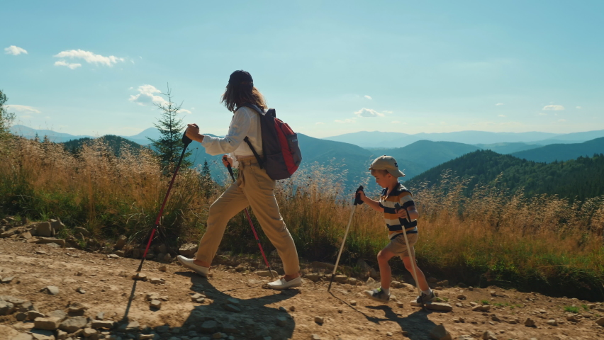 Active mother with her little son climbing mountain. Woman and child with trekking poles and backpack hike together along a rocky path Royalty-Free Stock Footage #1058382886