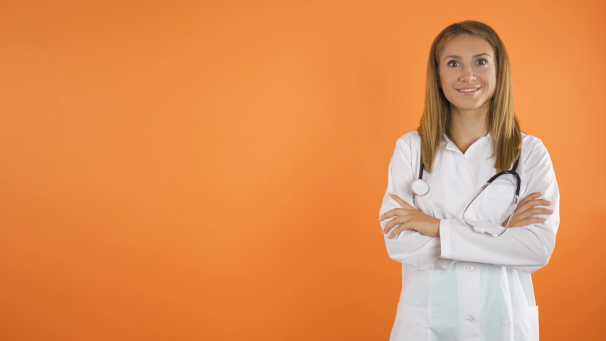 Women doctor smiles in front of the camera.Orange studio background Copy Space concept  Royalty-Free Stock Footage #1058384428