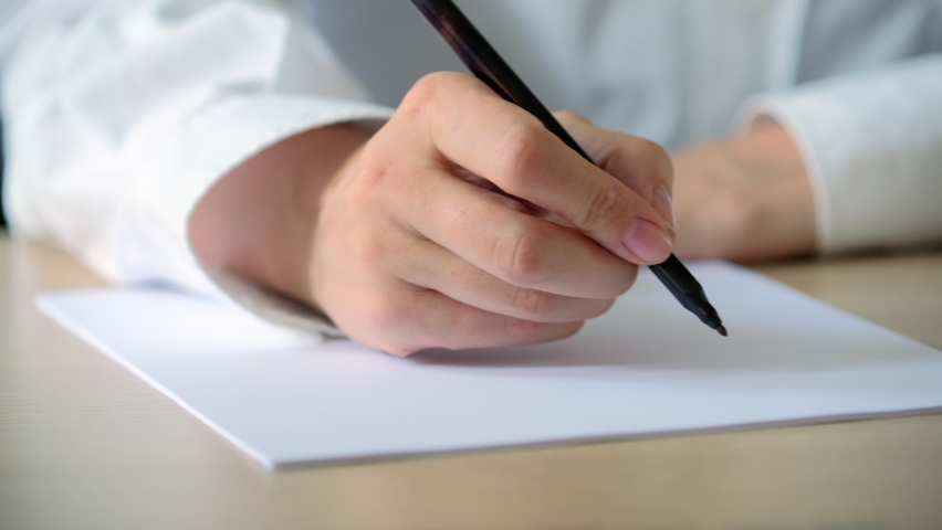 Woman writing letter on a piece of white paper. Closeup of female hands write notes. Writing essay or love letters Royalty-Free Stock Footage #1058384917