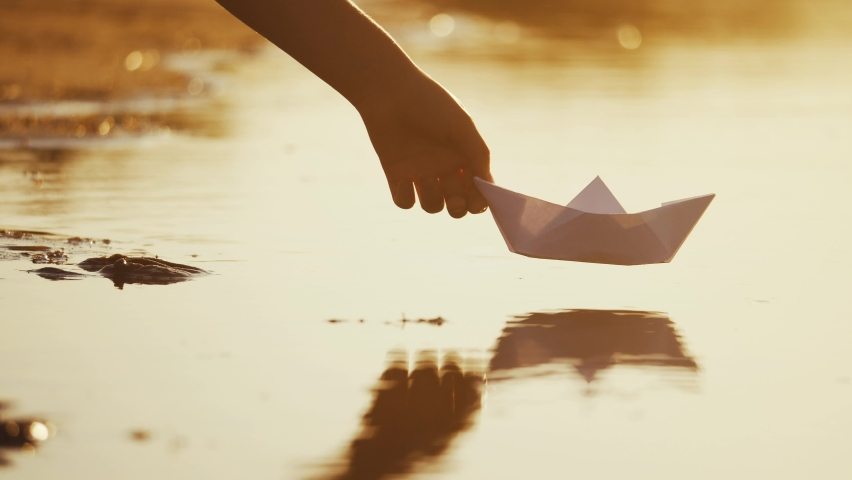 child puts a paper boat into the water. happy family fantasy kid dream concept. child playing with paper boat ship. a child hand launches a boat in a park in a lifestyle pond Royalty-Free Stock Footage #1058385352