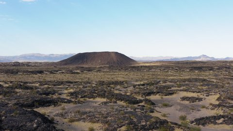 Low altitude aerial view approaching volcanic Amboy Crater in the Mojave Desert. Dramatic textured landscape.