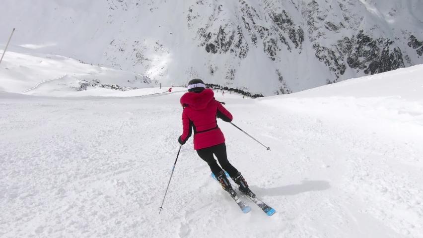 Girl skiing elegangt short turns on a steep ski-pist.