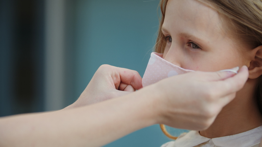 Close up of female hands put medical mask on face of little cute girl, protect from virus, take care of health of child outdoors, modern family life in pandemic epidemic of respiratory disease #1058397913