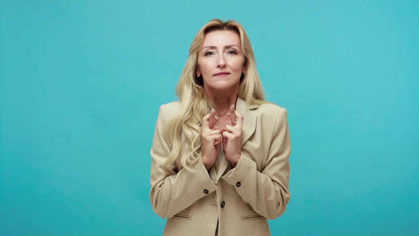 Nervous excited adult blond woman in business style suit crossing fingers dreaming about victory, sincerely rejoicing when winning, success symbol. Indoor studio shot isolated on blue background