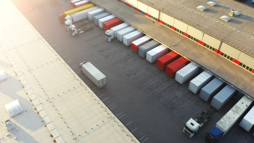 Semi truck with cargo trailer is travelling on a parking lot along a warehouse of a logistics park.  Aerial following shot  Royalty-Free Stock Footage #1058410912