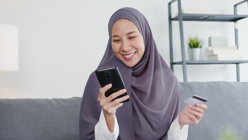 Asia muslim lady use smart phone, credit card buy and purchase e-commerce internet in living room at house. Stay at home, online shopping, self isolation, social distance, quarantine for coronavirus. Royalty-Free Stock Footage #1058412076