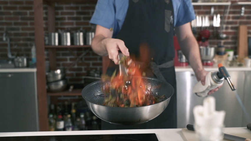 Chef Preparing Vegetables In Flambe Style. Cooking Delicious Food In Restaurant Kitchen. Cook Making Dinner In Asian Cuisine Eatery. Gourmet Meal Food Recipe. Food Preparation. Vegetarian Kitchen. | Shutterstock HD Video #1058412571