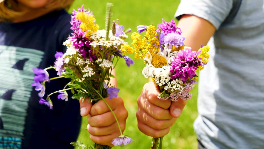 Children giving colorful flowers to camera